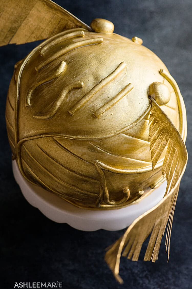 Fondant details on golden snitch cake