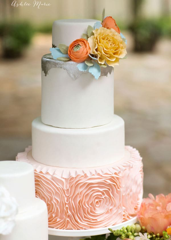 The show stopper is the largest tier with a gorgeous fondant rosette base and topped with some jagged silver leafing details and gumpaste flowers