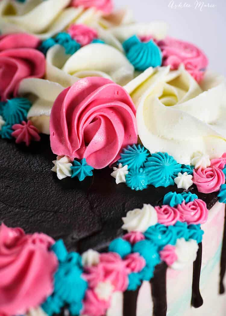 this buttercream gender reveal cake features white, pink and blue rosettes, drop flowers and stars - video tutorial