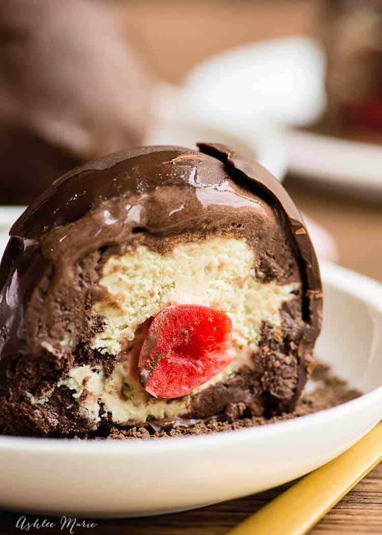 This delicious Italian dessert is two layers of gelato - any flavor - with a maraschino cherry center and covered with a hard chocolate shell | ashlee marie | ice cream | tartufo | italian | dessert | #ashleemarie #gelato #icecream #dessert