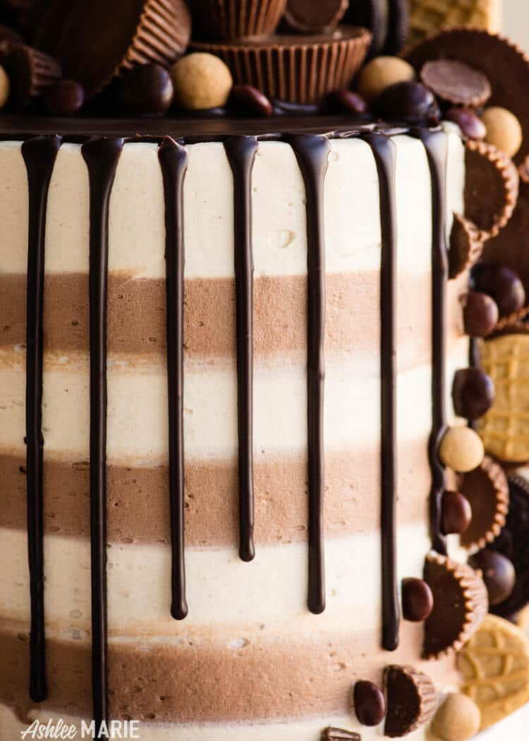 peanut butter cake with striped frosting and ganache drip